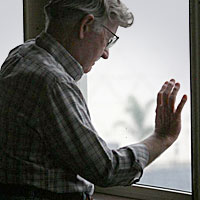 Man standing at window looking out